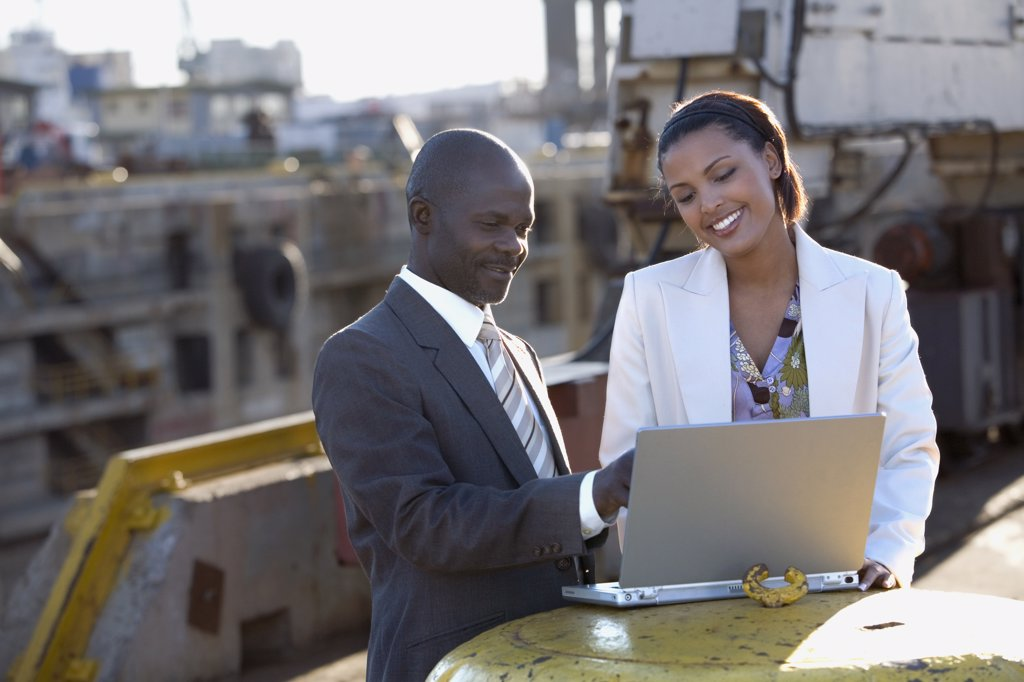 African American businesspeople looking at laptop : Stock Photo