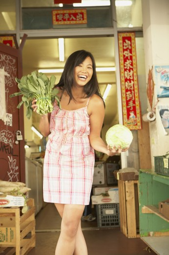 Stock Photo: 1589R-51403 Asian woman holding fresh vegetables
