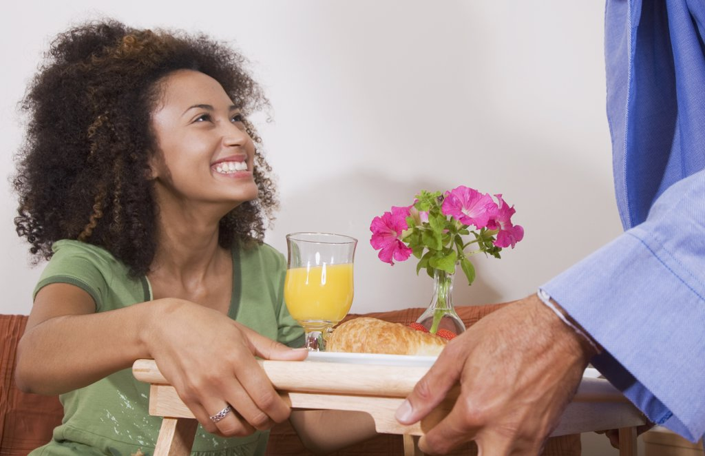 Stock Photo: 1589R-51535 African man bringing breakfast in bed to wife