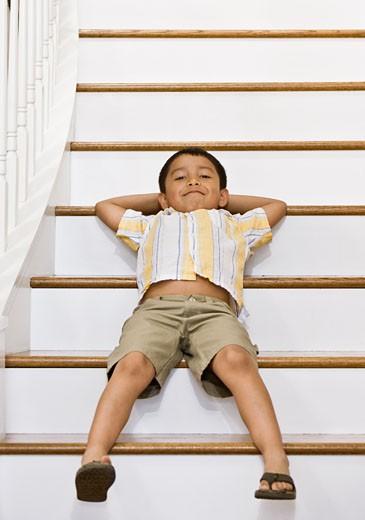 Stock Photo: 1589R-51772 Hispanic boy laying on stairs