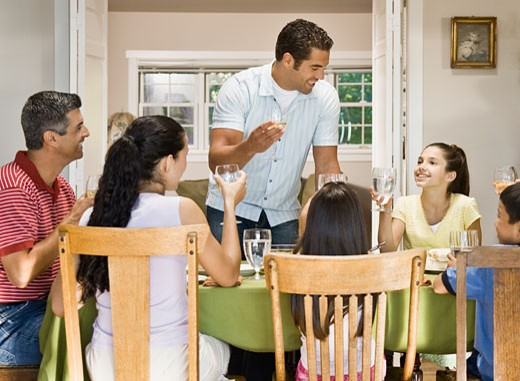 Stock Photo: 1589R-51813 Hispanic family toasting at dinner table