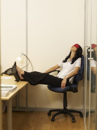 Hispanic businesswoman relaxing at desk : Stock Photo