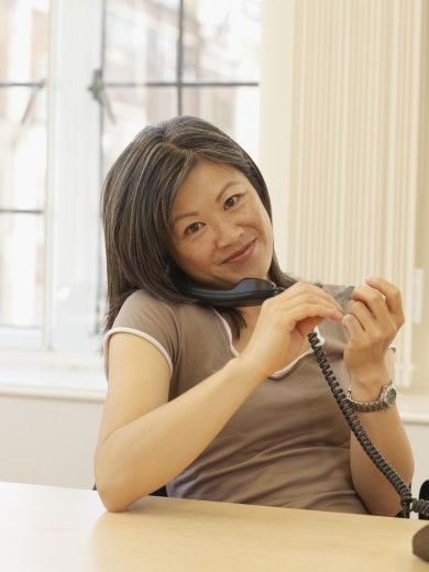 Stock Photo: 1589R-51956 Asian businesswoman talking on telephone