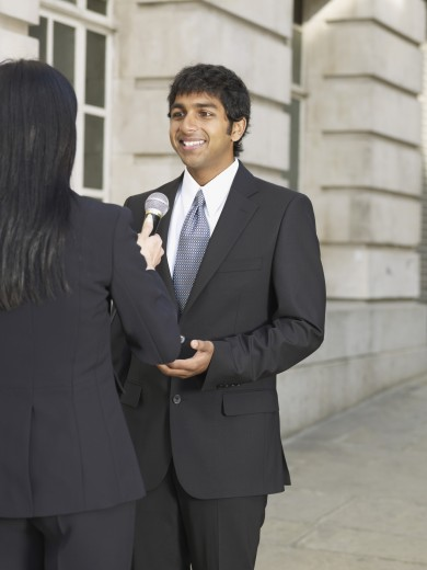 Stock Photo: 1589R-51981 Indian businessman being interviewed on sidewalk