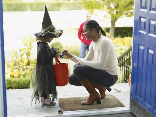 Stock Photo: 1589R-52428 African woman giving candy to trick or treater