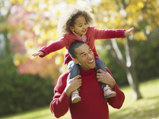 Stock Photo: 1589R-52436 African father carrying daughter on shoulders