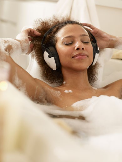African woman listening to music in bath : Stock Photo