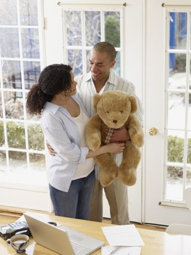 Pregnant African couple holding teddy bear : Stock Photo