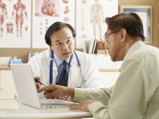 Stock Photo: 1589R-52559 Asian male doctor talking to patient
