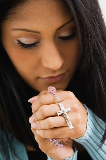 Stock Photo: 1589R-52694 Hispanic woman holding rosary beads