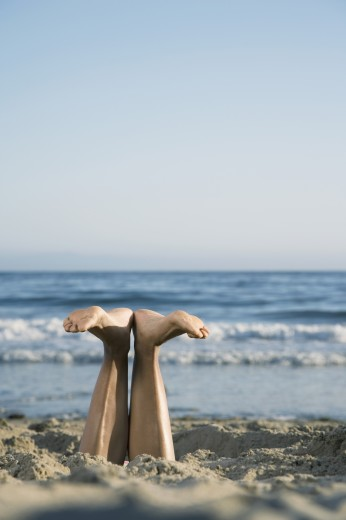 Stock Photo: 1589R-52815 Mixed Race woman's feet sticking out of sand