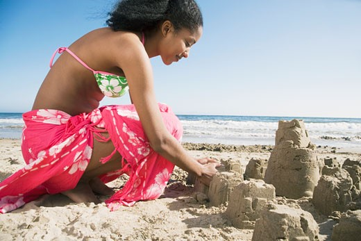 African woman building sand castles : Stock Photo