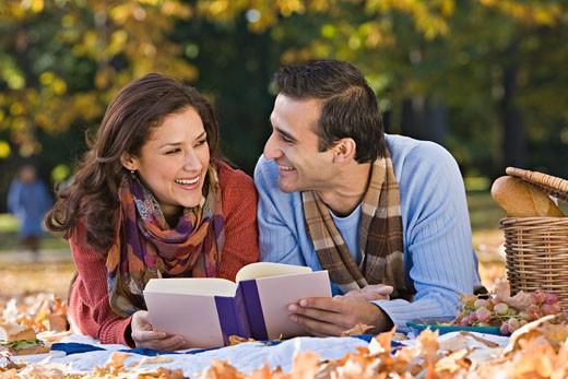 Stock Photo: 1589R-53280 Hispanic couple reading on picnic blanket