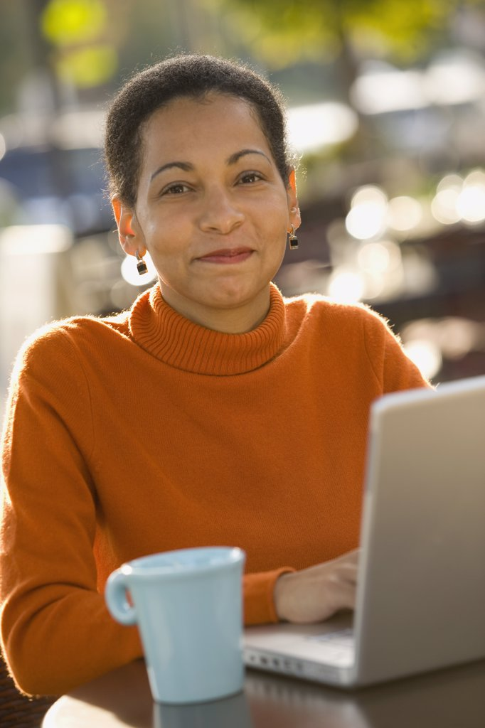 African woman typing on laptop : Stock Photo