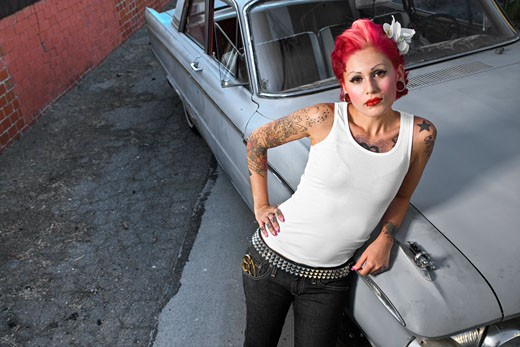 Stock Photo: 1589R-53410 Tattooed Hispanic woman leaning on car