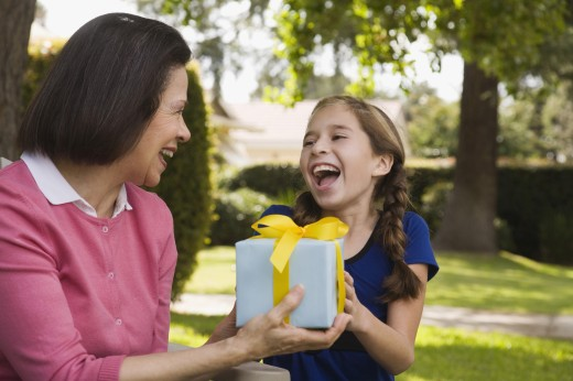Stock Photo: 1589R-53423 Hispanic grandmother and granddaughter exchanging gift