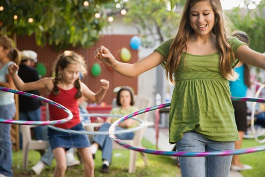 Hispanic girls playing with hula hoops : Stock Photo