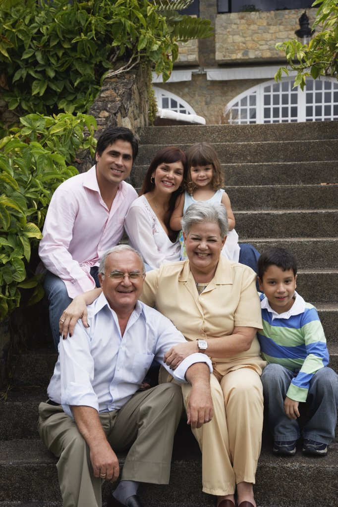 Multi-generational Hispanic family sitting on steps : Stock Photo