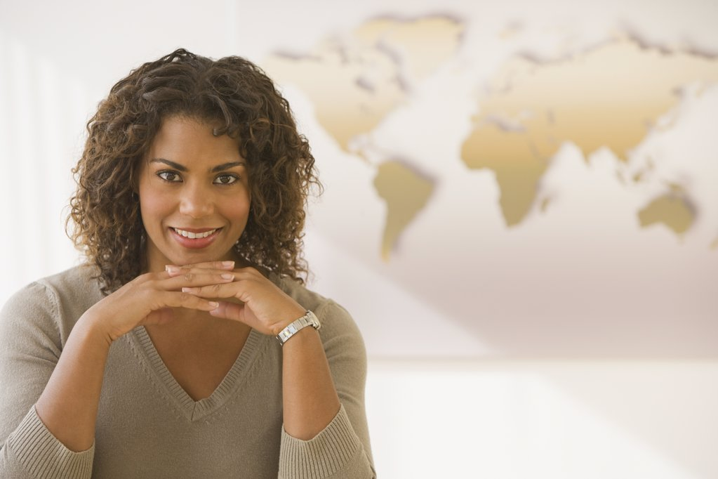 African businesswoman in front of world map : Stock Photo