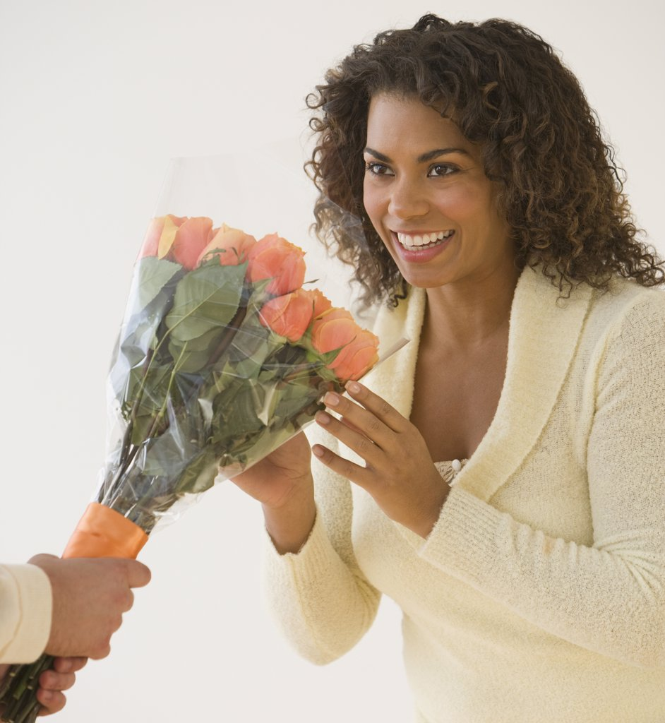 African woman receiving bouquet of flowers : Stock Photo