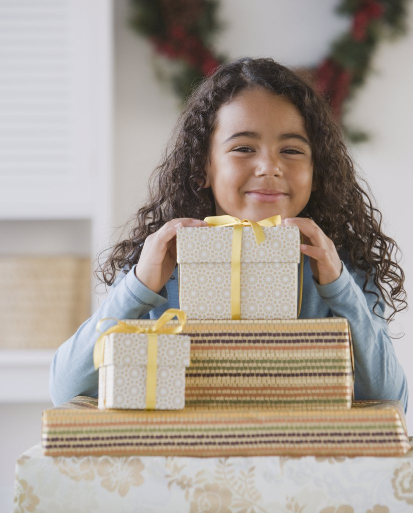 African girl behind stack of gifts : Stock Photo