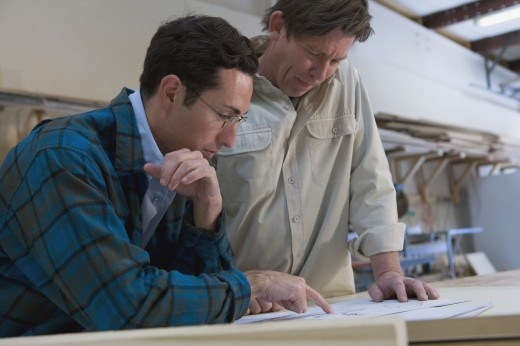 Stock Photo: 1589R-53824 Multi-ethnic men looking paperwork in wood shop