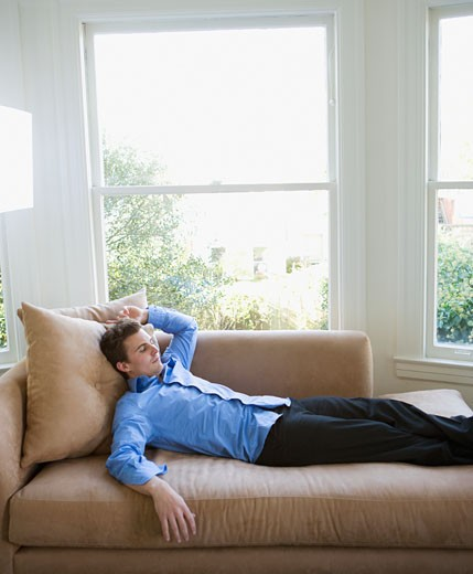 Stock Photo: 1589R-53896 Hispanic businessman laying on sofa