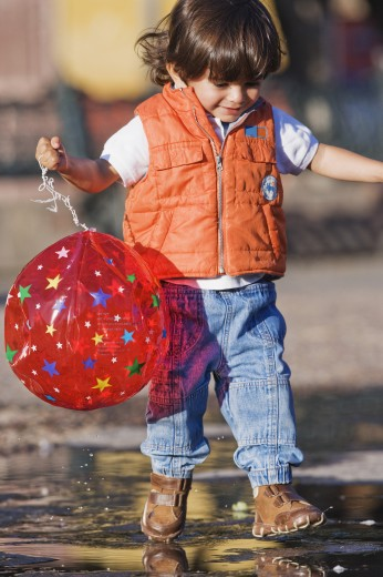 Hispanic boy walking in puddle : Stock Photo