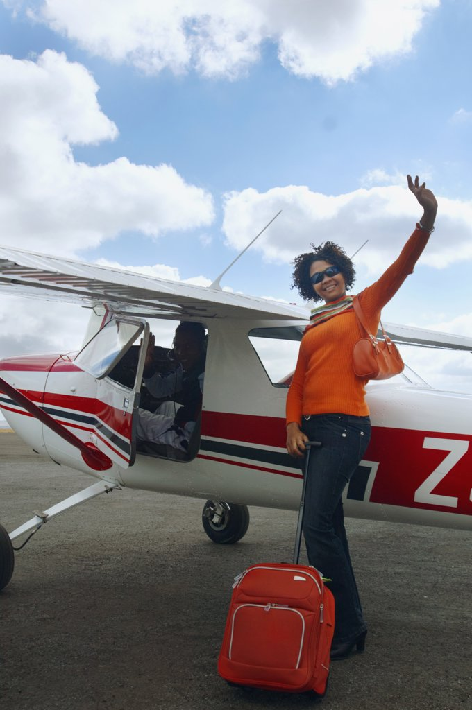 Stock Photo: 1589R-54104 African woman with suitcase next to airplane