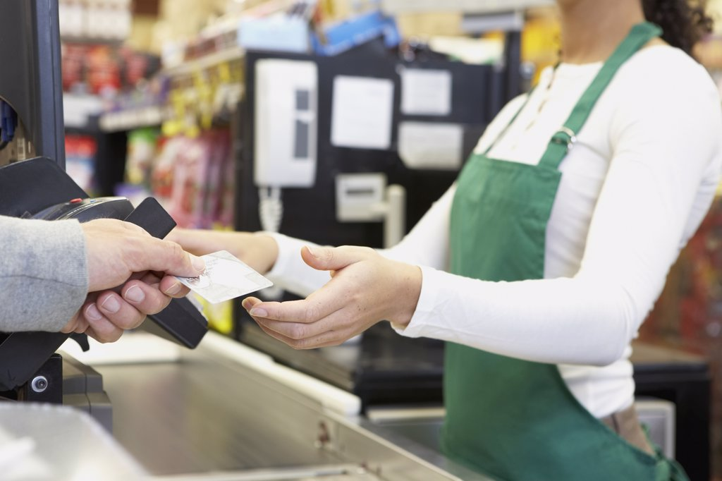 Stock Photo: 1589R-54132 Man paying with credit card at grocery store