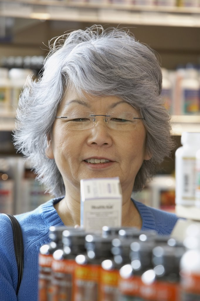 Stock Photo: 1589R-54202 Senior Asian woman reading vitamin label