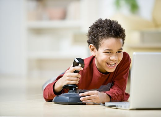 Stock Photo: 1589R-54608 African boy playing video games