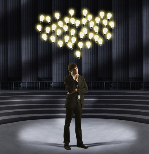 Stock Photo: 1589R-54667 European businessman standing under floating light bulbs