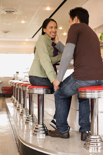 Stock Photo: 1589R-54823 Asian couple holding hands at diner