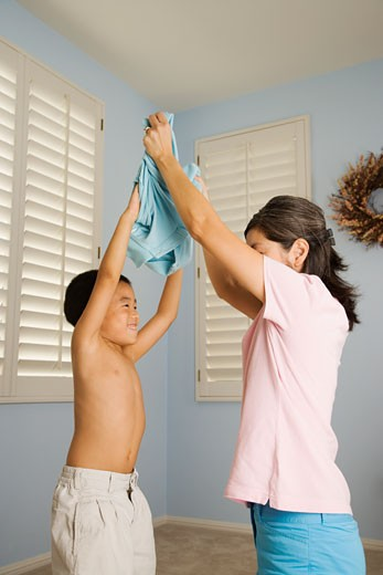 Stock Photo: 1589R-54897 Asian mother helping son take off shirt