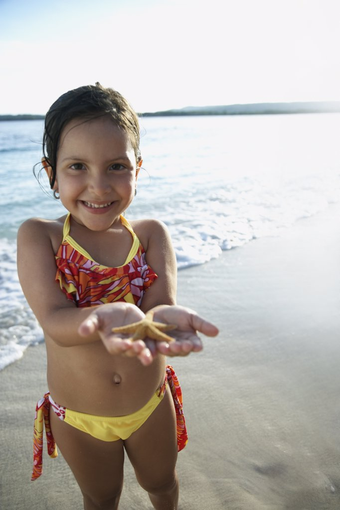 Stock Photo: 1589R-54968 Hispanic girl holding starfish