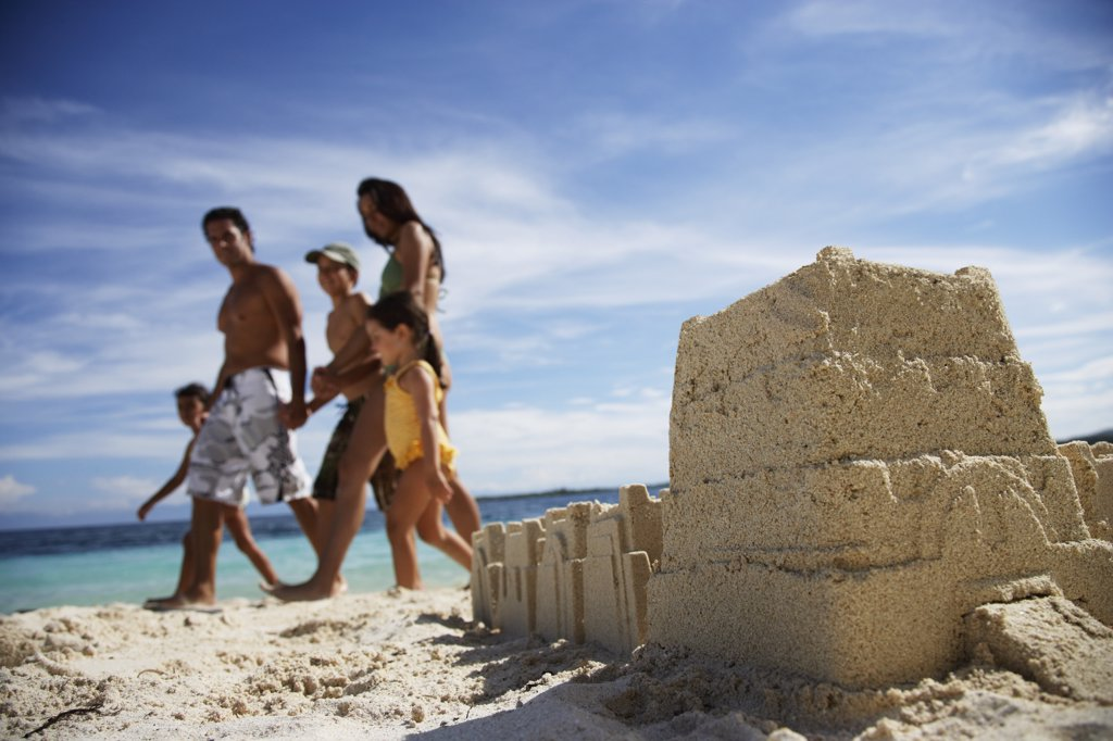 Stock Photo: 1589R-54972 Hispanic family walking past sandcastle