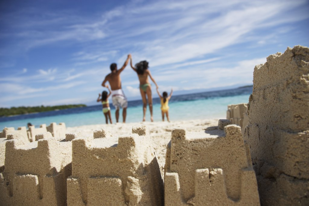 Hispanic family with sand castle in foreground : Stock Photo