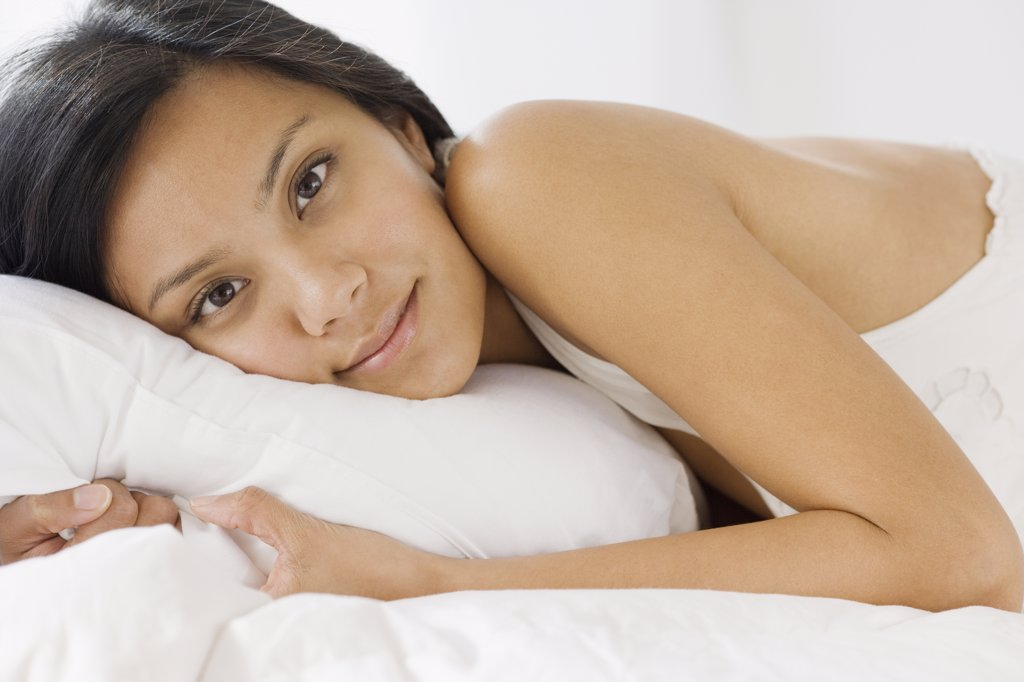 Pacific Islander woman laying on bed : Stock Photo