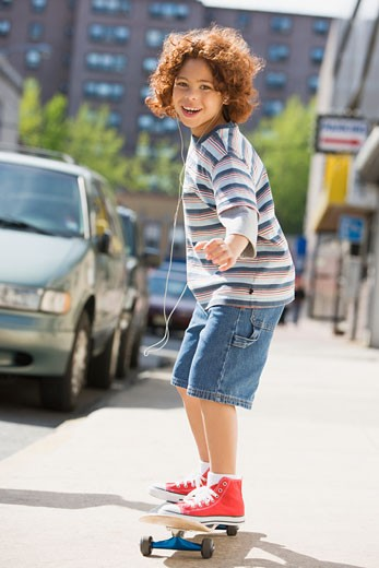 Mixed Race boy riding skateboard : Stock Photo