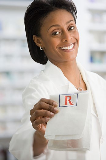 African female pharmacist handing over prescription : Stock Photo