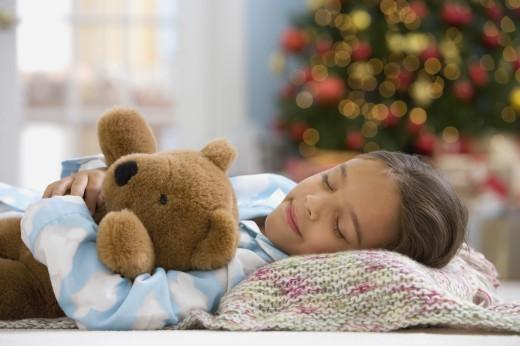 Hispanic girl sleeping in front of Christmas tree : Stock Photo