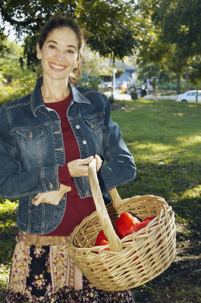 Middle Eastern woman carrying basket of organic produce : Stock Photo