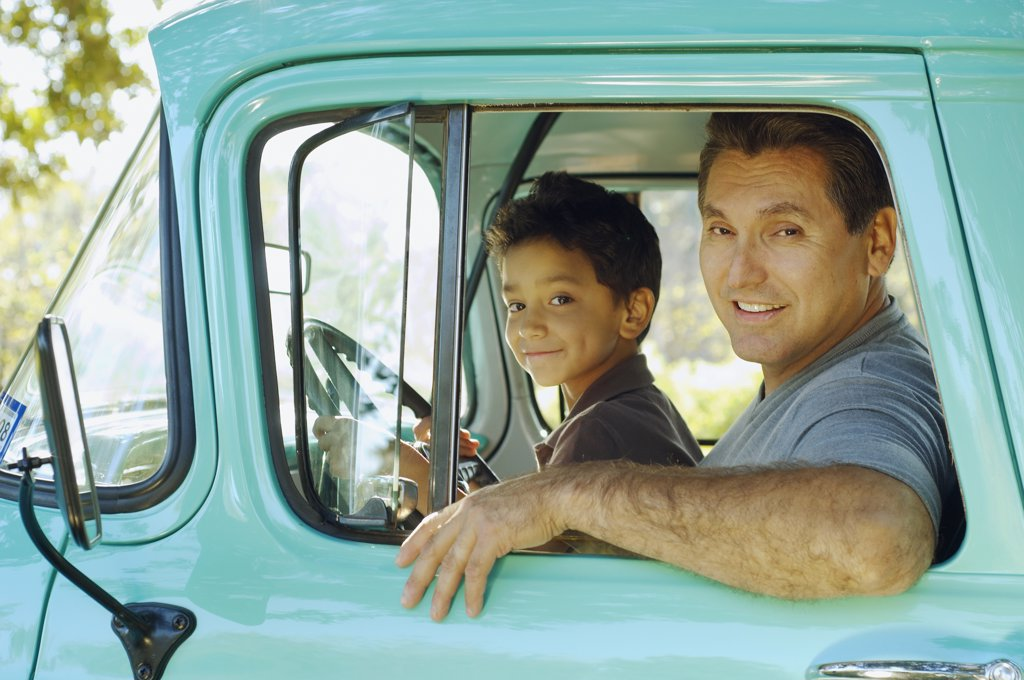 Hispanic father and son sitting in truck : Stock Photo