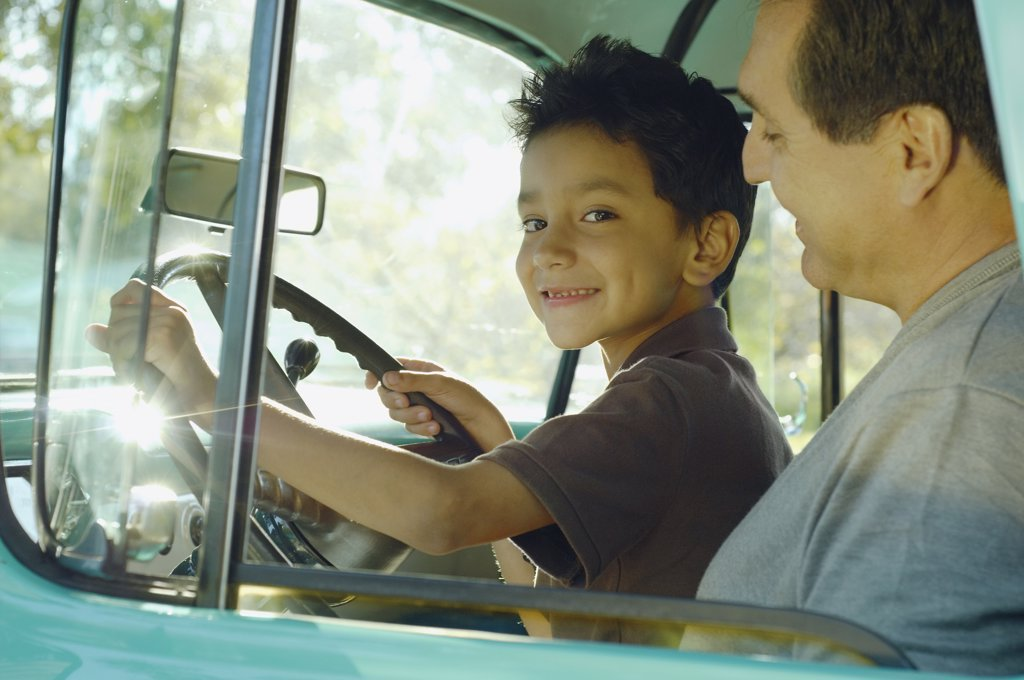 Stock Photo: 1589R-55467 Hispanic father and son sitting in truck