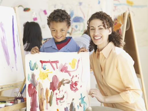 Stock Photo: 1589R-55485 Hispanic female art teacher and male student holding painting