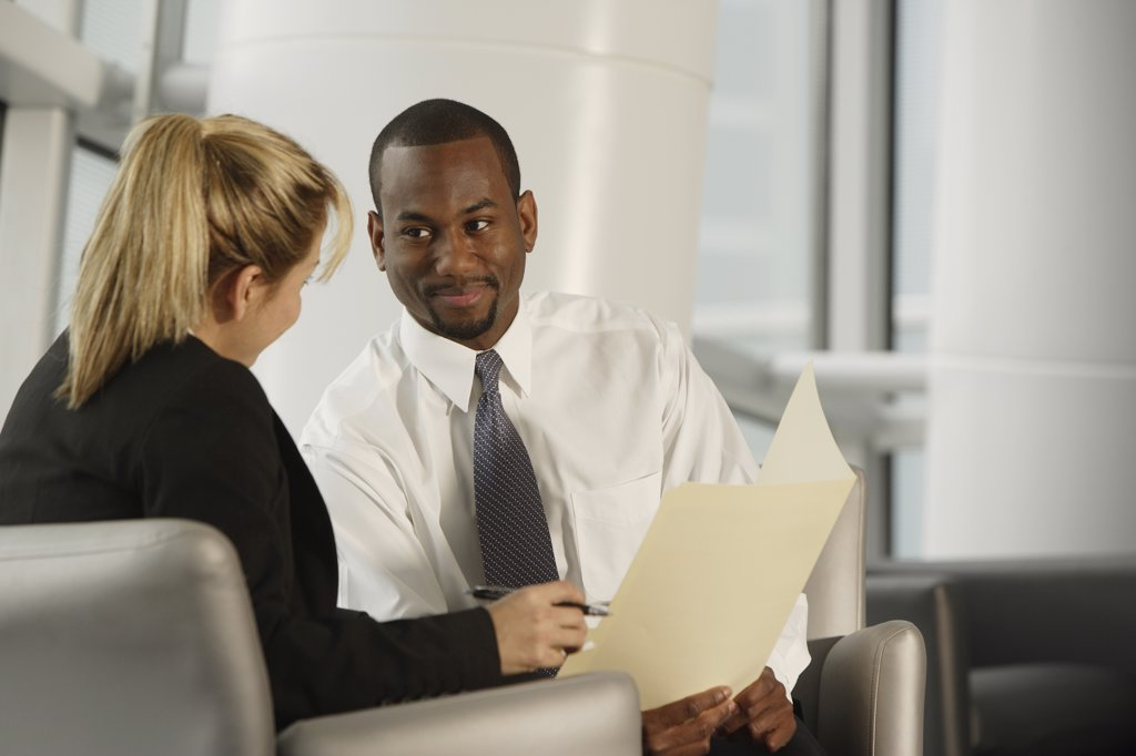 Multi-ethnic businesspeople discussing paperwork : Stock Photo