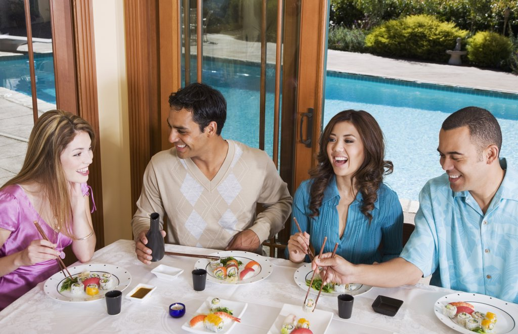 Multi-ethnic couples eating sushi : Stock Photo