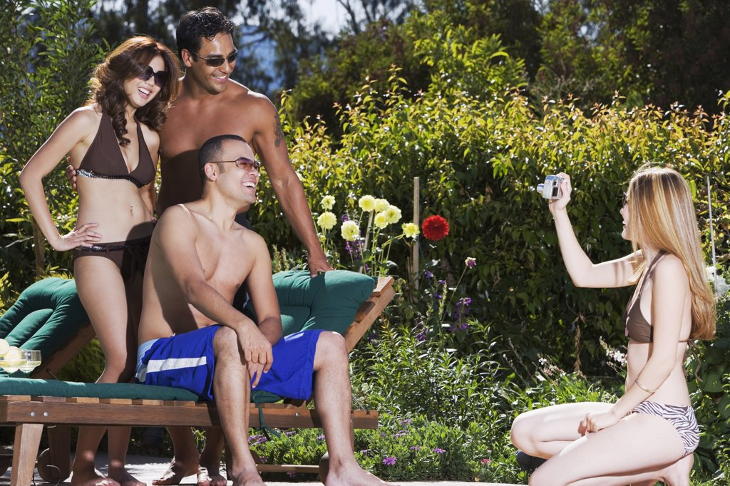 Pacific Islander woman taking photograph of friends : Stock Photo