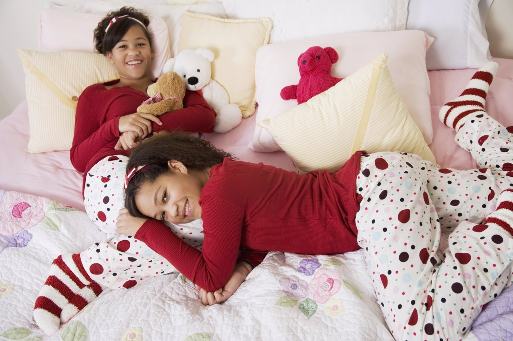 African twin sisters laying on bed : Stock Photo